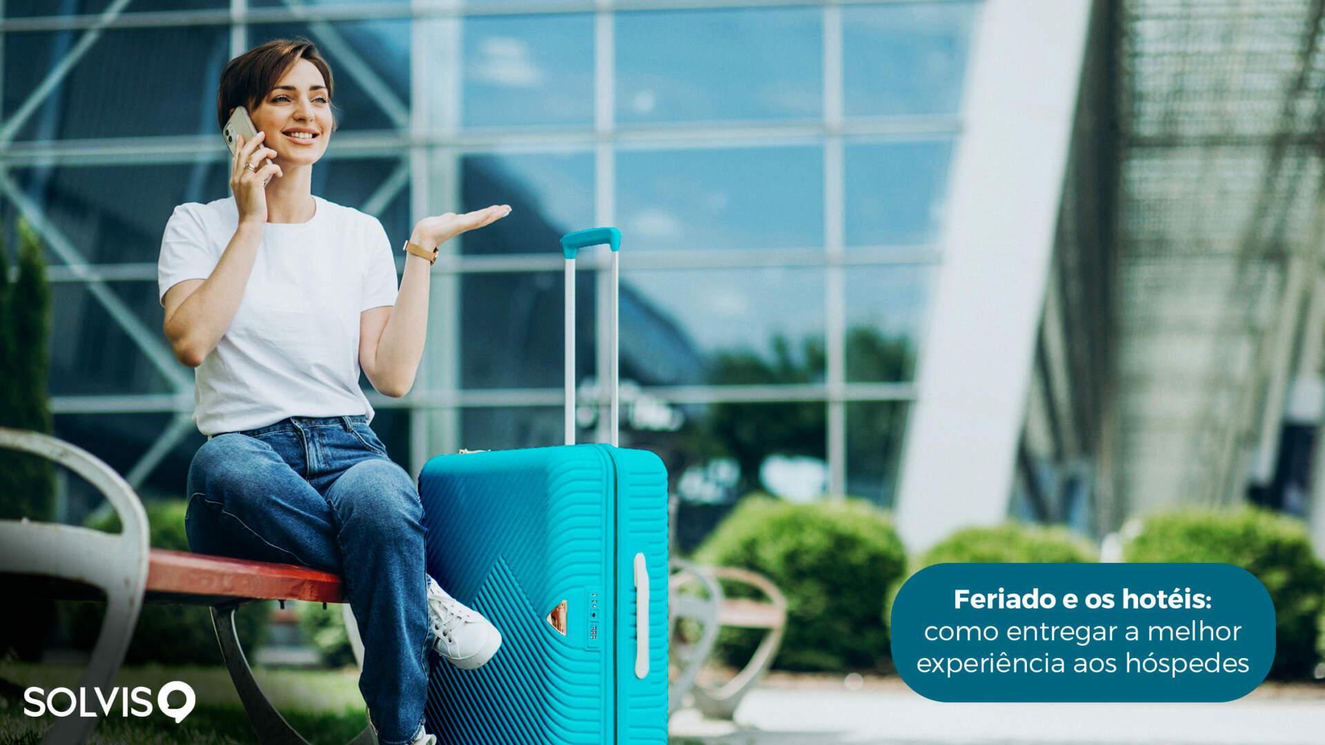 Mulher sentado em um banco ao ar livre, falando ao telefone com a sua mala de viagem azul ao lado